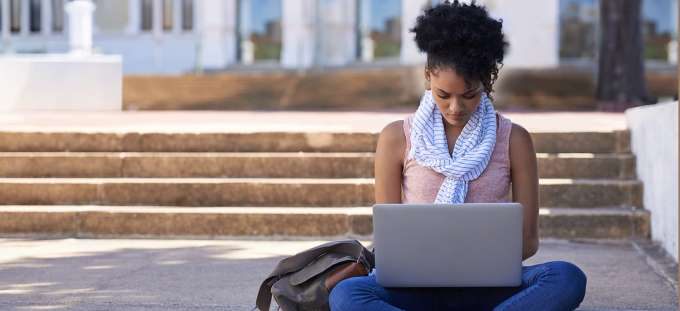 UF Wildlife Forensic Sciences and Conservation An woman sitting on the steps of her college doing research on her laptop